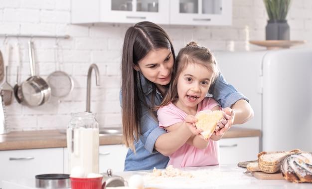Szczęśliwa mama z córką przygotowująca domowe ciasta na tle jasnej kuchni.