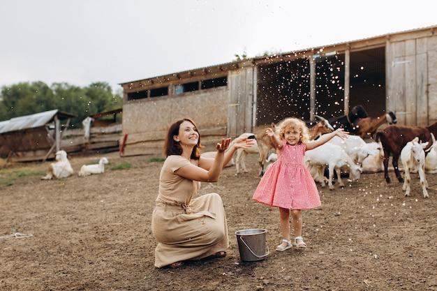 Szczęśliwa mama z córką spędzają czas na ekologicznej farmie wśród kóz.