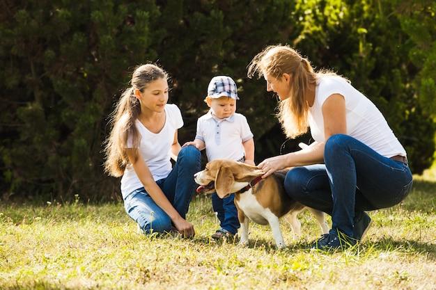Szczęśliwa mama z córką, synkiem i psem beagle na spacer