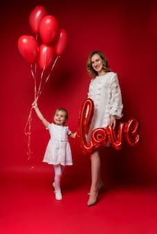 Szczęśliwa mama z miłością balonu foliowego i córką z naręczem czerwonych balonów na czerwono