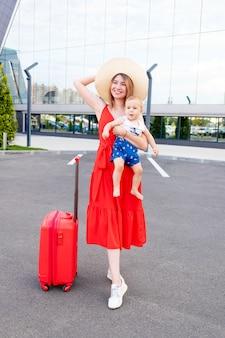 Szczęśliwa mama z synkiem na lotnisku z czerwoną walizką jedzie latem na wycieczkę lub wakacje