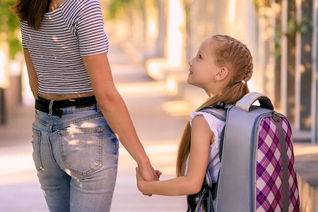 Szczęśliwa mama zabiera małą uczennicę do szkoły