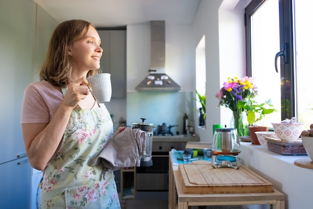 Szczęśliwa marzycielska gospodyni domowa w fartuchu, pije herbatę i wygląda przez okno w swojej kuchni. gotowanie w domu i koncepcja przerwa na herbatę