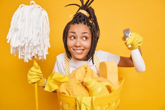 Szczęśliwa marzycielska kobieta z dredami trzyma mop i detergent