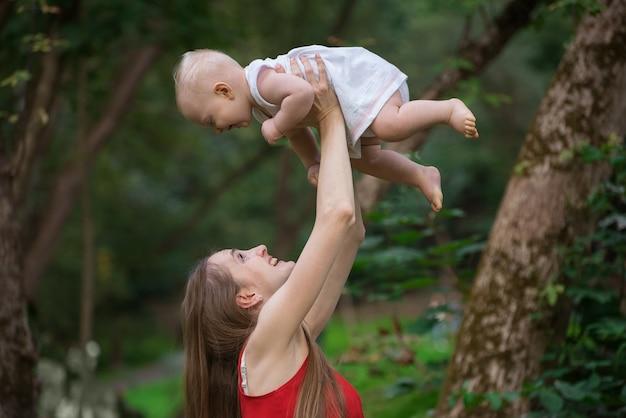 Szczęśliwa matka bawić się z jej dzieckiem outdoors. koncepcja wspólnoty z dzieckiem.