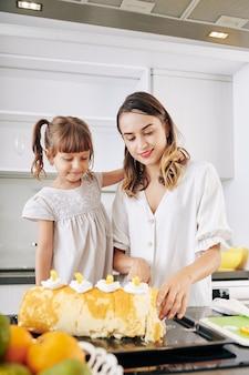 Szczęśliwa matka i córka cięcia zdobione szwajcarskie rolki mandarynki zrobiły w domu