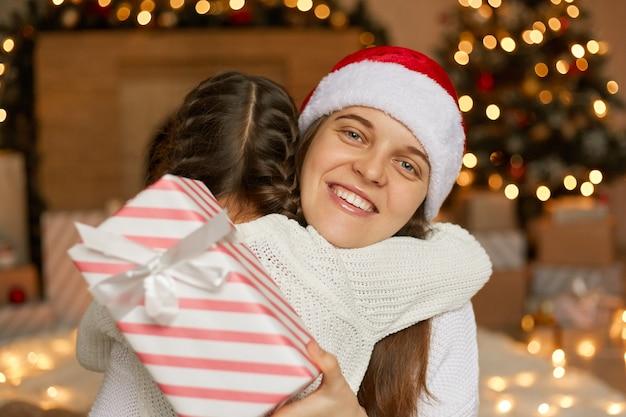 Szczęśliwa matka i córka, dając sobie nawzajem świąteczny prezent i przytulanie, mama w czapce mikołaja i uśmiechnięta, rodzina pozuje w domu w świątecznym pokoju.