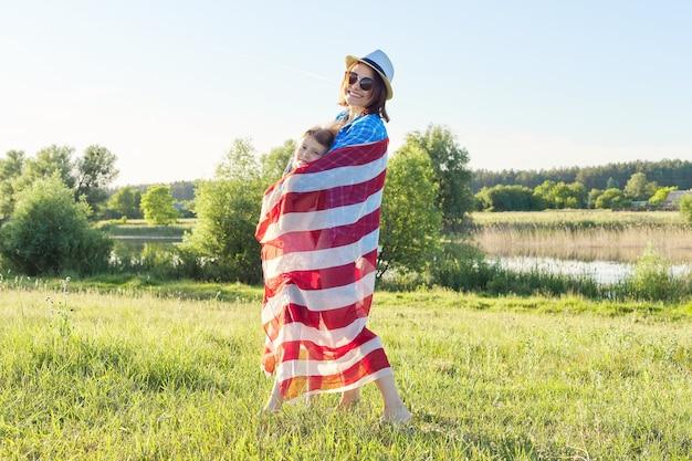 Szczęśliwa matka i córka dziecko dziewczynka przytulanie pod amerykańską flagą, usa, 4 lipca, lato natura tło