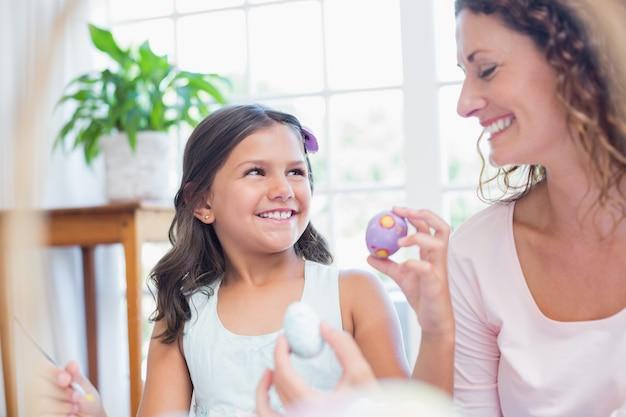Szczęśliwa matka i córka maluje easter jajka