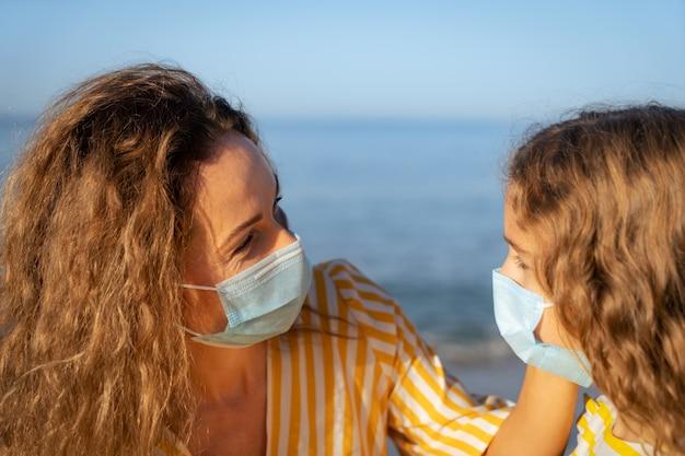 Szczęśliwa matka i córka noszenie maski medyczne na zewnątrz przeciw błękitne niebo.