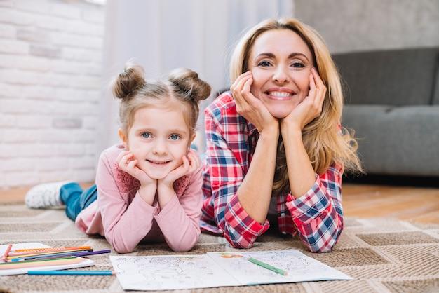 Szczęśliwa matka i córka patrzeje kamerę w żywym pokoju