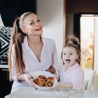 Szczęśliwa matka i córka pokazuje piec twarogowego fritter