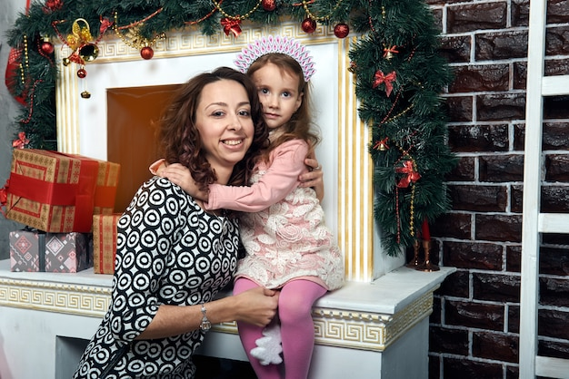 Szczęśliwa matka i córka przy kominku na ferie zimowe. wigilia i sylwester.