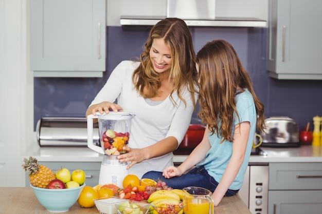 Szczęśliwa matka i córka przygotowuje sok owocowy