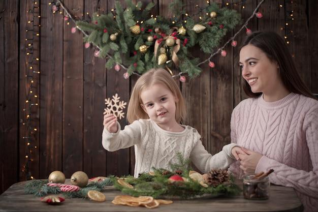 Szczęśliwa matka i córka robią świąteczny wieniec