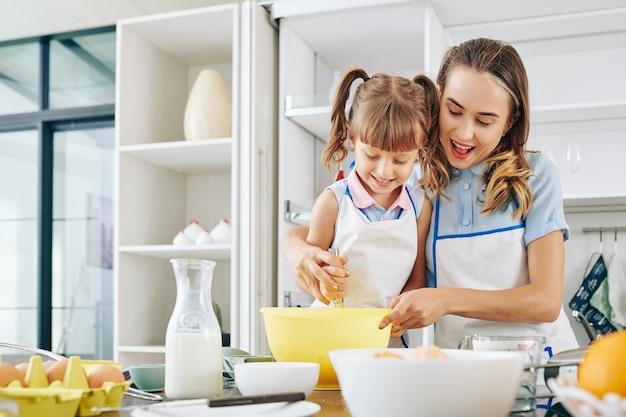 Szczęśliwa matka i córka spędzają razem weekend i robią naleśniki na śniadanie