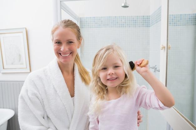 Szczęśliwa matka i córka szczotkuje włosy