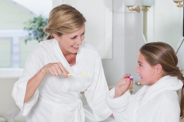Szczęśliwa matka i córka szczotkuje zęby wpólnie
