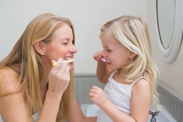 Szczęśliwa matka i córka szczotkuje zęby