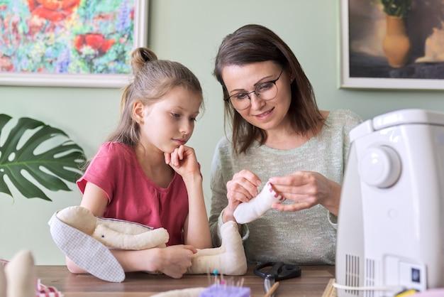 Szczęśliwa matka i córka szycie razem zabawka lalka króliczek w domu. rodzina, hobby i wypoczynek, kreatywność, styl życia, umiejętności i nauka, komunikacja rodzic-dziecko, dzień matki