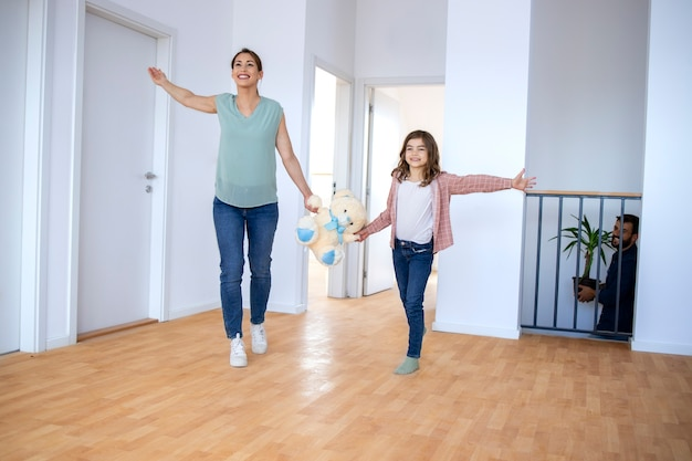 Szczęśliwa matka i córka trzymając pluszowego misia i uczucie podekscytowania podczas przeprowadzki do nowego domu.