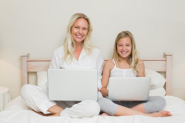Szczęśliwa matka i córka używa laptopy w łóżku