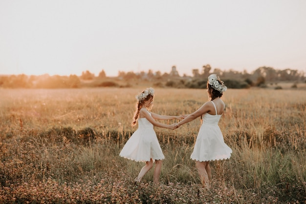 Szczęśliwa matka i córka w białych sukienkach wirują, a latem mają radość i szczęście