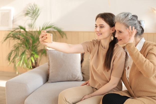 Szczęśliwa matka i córka w średnim wieku biorąc selfie w domu.