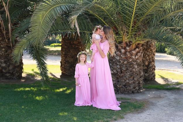 Szczęśliwa matka i córki w podobnych różowych sukienkach w stylu vintage