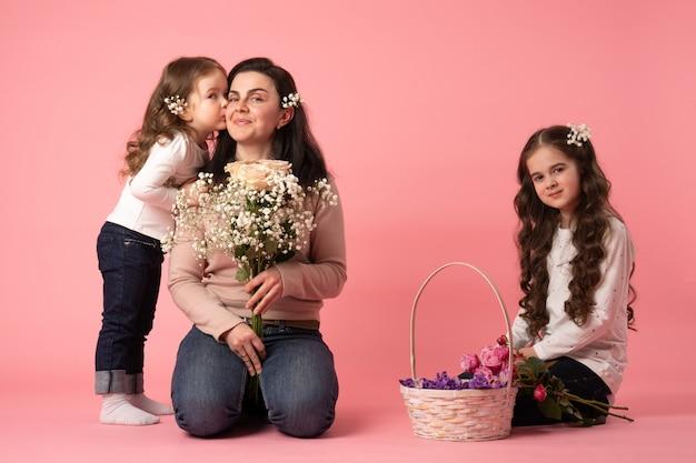 Szczęśliwa matka i córki z bukietem białych kwiatów. córka całuje matkę, dziewczyna siedzi na ziemi z koszem kwiatów. szczęśliwego dnia matki.