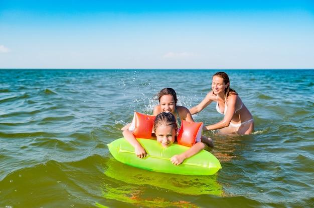 Szczęśliwa matka i dwie małe pozytywne córki kąpią się i pływają w morzu na dmuchanym materacu w słoneczny letni dzień. koncepcja wakacje z dziećmi. copyspace