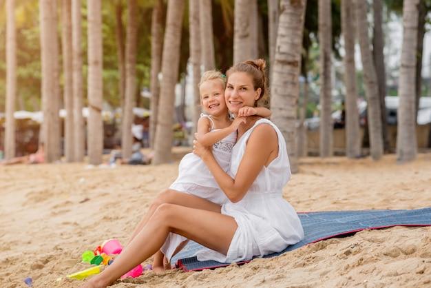 Szczęśliwa matka i dziecko na zmierzchu przy plażą.