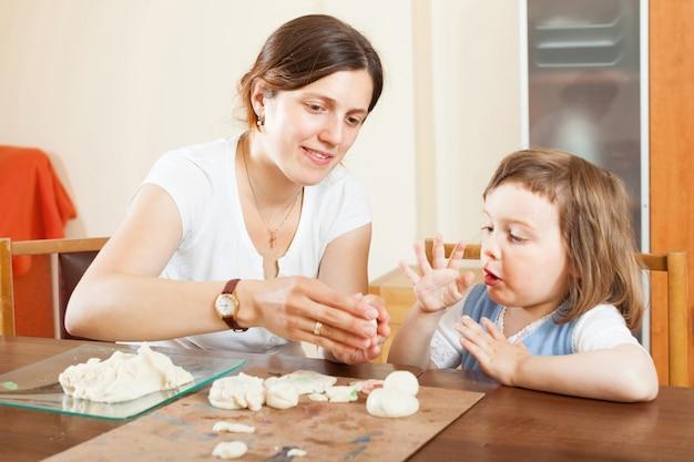 Szczęśliwa matka i dziecko rzeźbiarskie z gliny przy stole