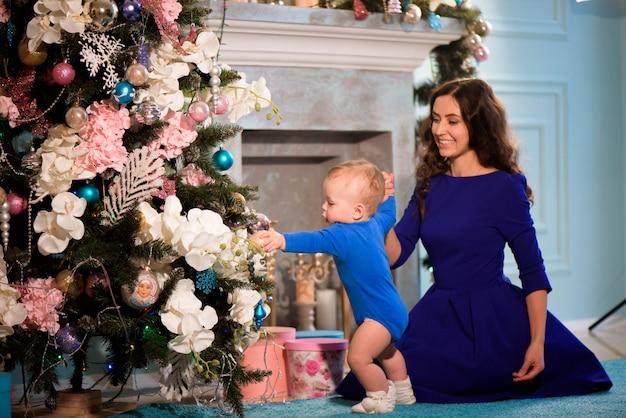 Szczęśliwa matka i dziecko świętują boże narodzenie. święta noworoczne.