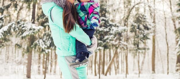 Szczęśliwa matka i dziecko w winter park. rodzina na zewnątrz. wesoła mamusia z dzieckiem.