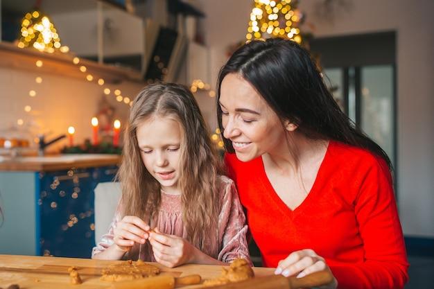 Szczęśliwa matka i dziewczynki gotowanie świątecznych ciasteczek w kuchni