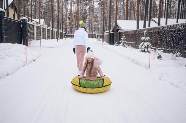 Szczęśliwa matka i mała śliczna dziewczynka w różowym ciepłym stroju wierzchnim, chodzenie, zabawa jeździ nadmuchiwaną rurą śnieżną w śnieżnobiałym zimnym lesie na zewnątrz