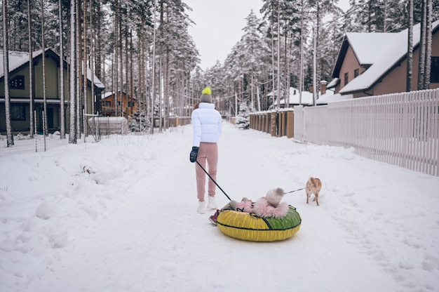 Szczęśliwa matka i mała urocza dziewczynka w różowym ciepłym stroju wierzchnim, chodzenie, zabawa jeździ nadmuchiwaną rurą śnieżną z czerwonym psem shiba inu w śnieżnobiałej zimowej wsi na zewnątrz