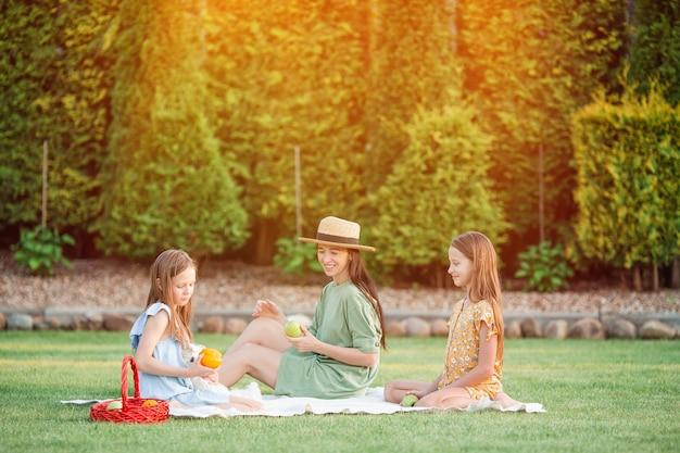 Szczęśliwa matka i małe córki relaksuje nad jeziorem