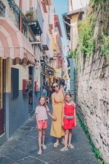 Szczęśliwa matka i małe urocze dzieci na wygodnej ulicy podczas włoskich wakacji.