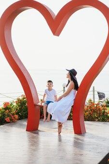 Szczęśliwa matka i syn siadają na wielkiej rzeźbie z czerwonym sercem nad morzem