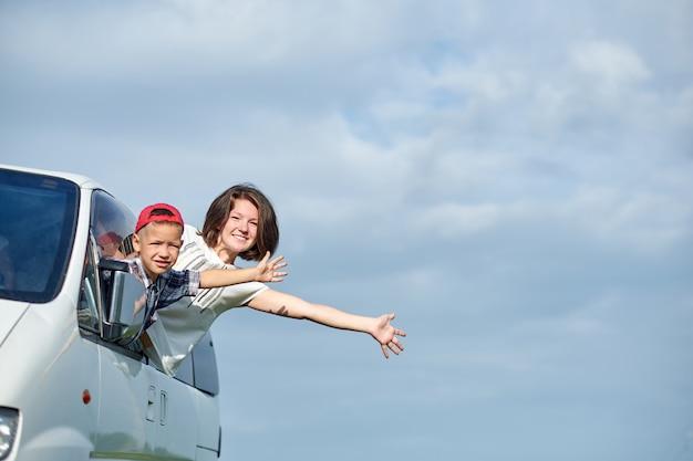 Szczęśliwa matka i syn spoglądający z okien i cieszący się wycieczką samochodową. rodzina podróżująca samochodem