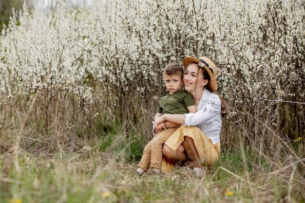 Szczęśliwa matka i syn zabawy razem. matka delikatnie obejmuje syna. w tle kwitną białe kwiaty.