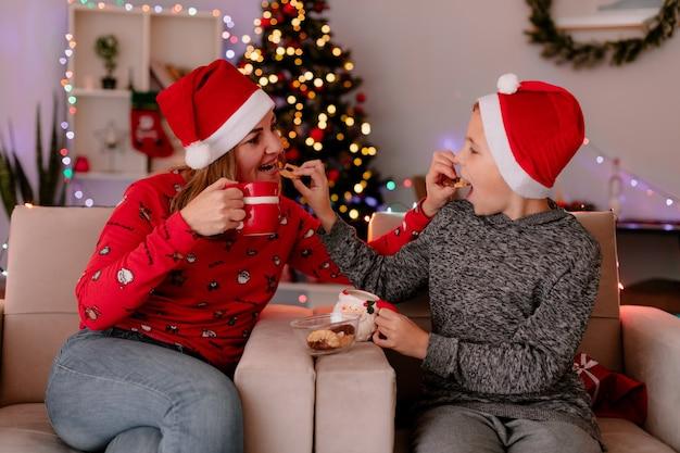 Szczęśliwa matka i synek w czapkach mikołaja z filiżankami herbaty jedzą ciasteczka siedząc na kanapie, bawiąc się w urządzonym pokoju z choinką w tle