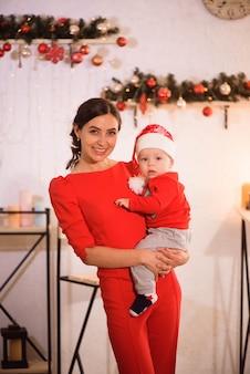 Szczęśliwa matka i urocze dziecko w santa hat świętować boże narodzenie. święta noworoczne. maluch z mamą w odświętnie urządzonym pokoju