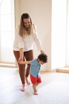 Szczęśliwa matka kaukaski trzymając się za ręce syna i pomagając mu chodzić. śliczny, kręcony chłopiec rasy mieszanej uczący się chodzenia boso po podłodze i zabawy. czas rodzinny, dzieciństwo i koncepcja pierwszego kroku