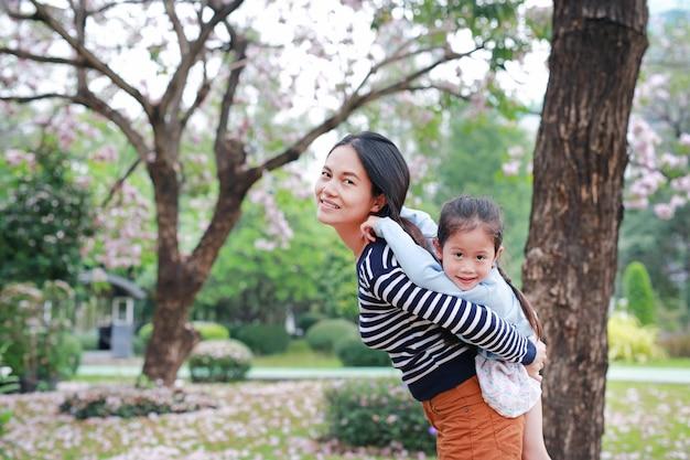 Szczęśliwa matka niesie jej córki w ogródzie z w pełni spadać różowym kwiatem wokoło. szczęśliwa kochająca rodzina.