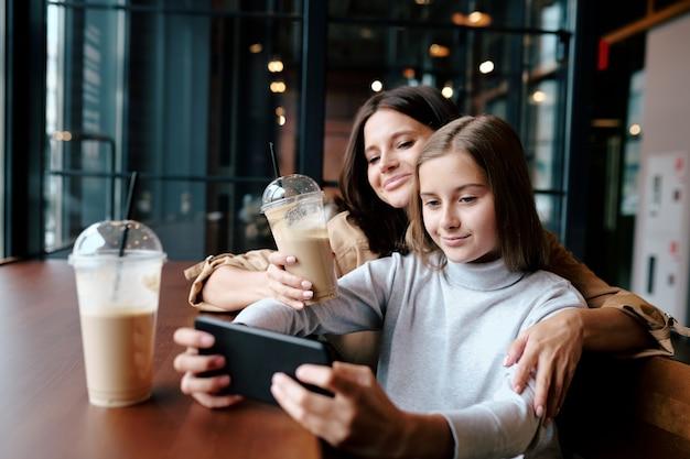 Szczęśliwa matka obejmująca swoją uroczą córkę smartfonem, jednocześnie oglądając wideo w kawiarni przy drinku