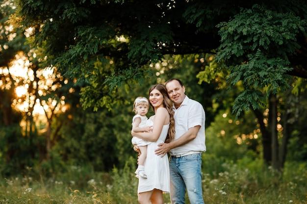 Szczęśliwa matka, ojciec i córeczka gra w parku latem