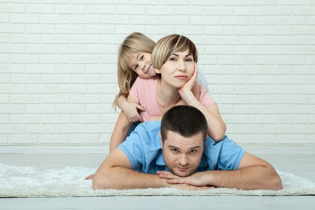 Szczęśliwa matka, ojciec i dziewczyna w domu na podłodze